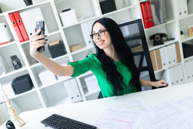 Una ragazza con gli occhiali si siede in ufficio al tavolo e si scatta foto al telefono.