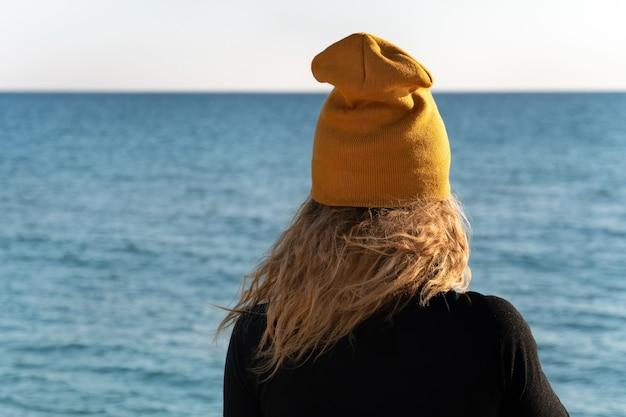 Una ragazza con i capelli biondi ricci in giacca sportiva nera e berretto giallo sta guardando il mare blu