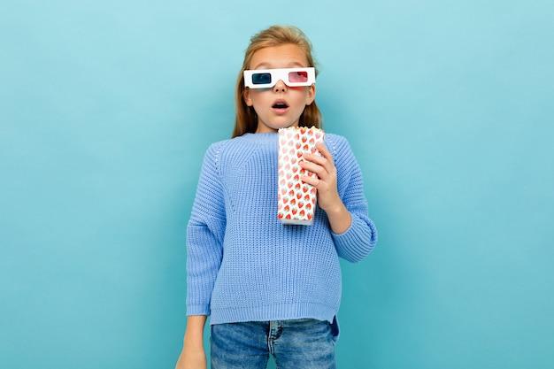 Una ragazza con il trucco e lunghi capelli castani, occhiali 3d sembra film o cartone animato con popcorn