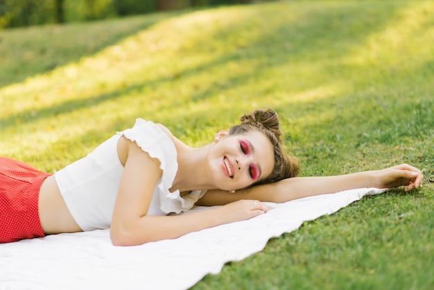 Una ragazza con il trucco luminoso giace su una coperta di abete sull'erba con gli occhi chiusi e sorridente. trucco estivo professionale in stile anguria