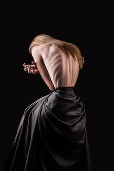Una ragazza con la schiena nuda, magrezza severa e costole sporgenti