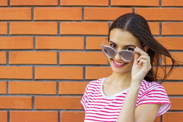 Una ragazza con lunghi capelli castani che indossa una maglietta a righe rosse e bianche