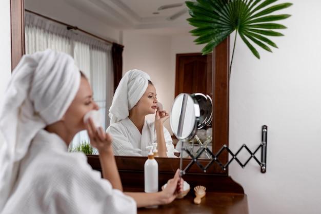 Una ragazza con un asciugamano in testa e in camice bianco seduto a un tavolo marrone