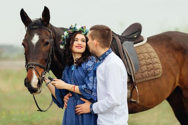 Una ragazza con un bel trucco e una ghirlanda di fiori in testa guarda il suo ragazzo e stanno in piedi accanto al cavallo
