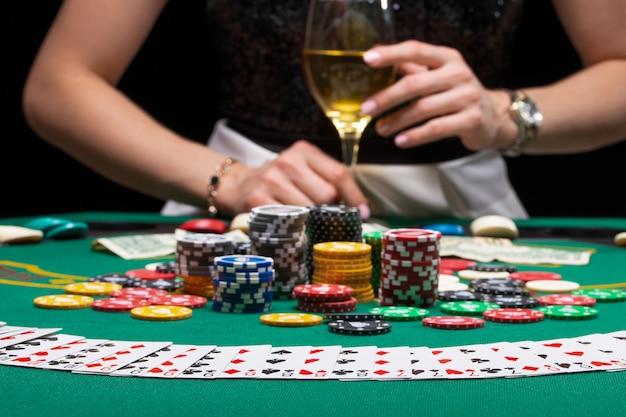 Una ragazza con un bicchiere di vino che gioca a poker