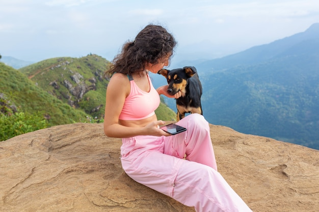 Una ragazza con un cane che gode del paesaggio montano sul bordo di una scogliera