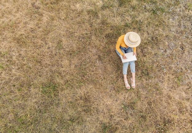 Una ragazza con un cappello disegna uno schizzo nella natura - una vista dall'alto