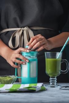 Una ragazza con un grembiule nero sta preparando un latte dal tè verde matcha.