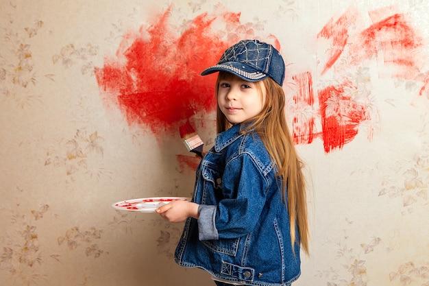 Una ragazza con un rullo di vernice e una vernice rossa tra le mani disegna la carta da parati nella stanza.
