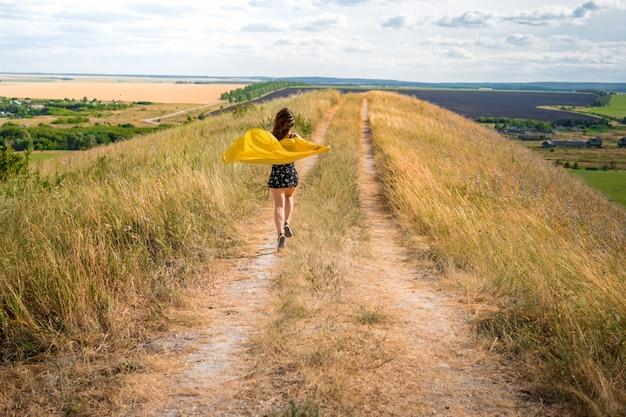 Una ragazza con un vestito e un mantello giallo che svolazza al vento corre lungo un sentiero rurale