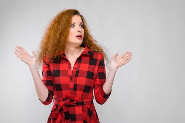 Una ragazza con una camicia a quadri allarga le braccia ai lati.