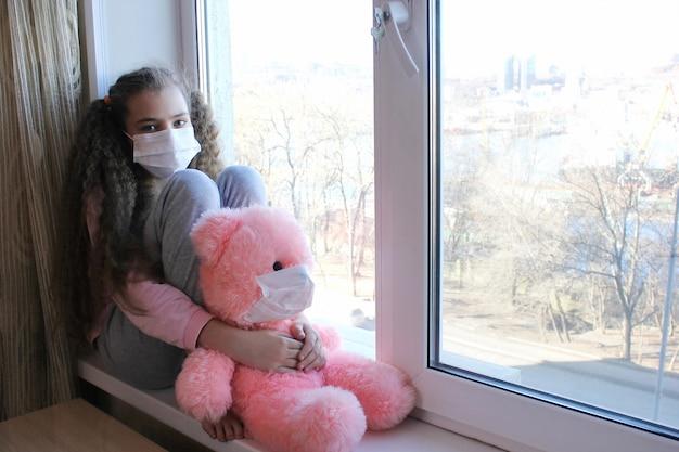 Una ragazza con una maschera protettiva sul viso si siede a casa sul davanzale della finestra e guarda fuori dalla finestra. una ragazza abbraccia un orso rosa giocattolo, che è anche in una maschera.