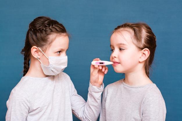 Una ragazza con una mascherina medica misura la temperatura di un'altra con un termometro in bocca. trattare i bambini