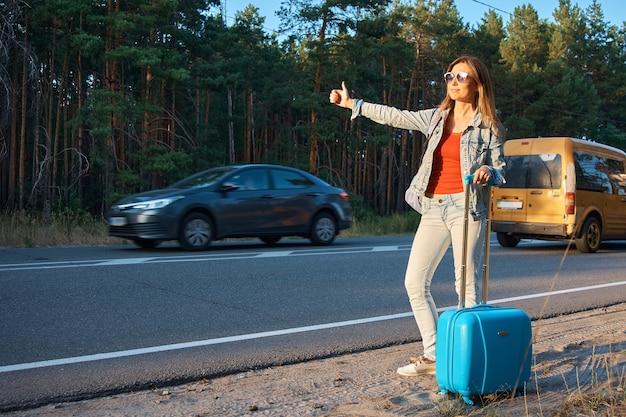 Una ragazza con una valigia fa l'autostop in macchina.