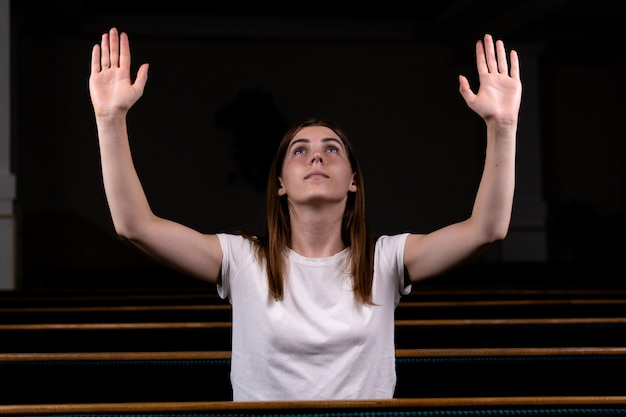 Una ragazza cristiana si siede con le mani in alto e il viso e prega con umile cuore in chiesa