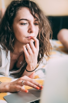 Una ragazza dai capelli ricci giace sul letto accanto a un laptop a casa e con una faccia seria legge le notizie del mondo.