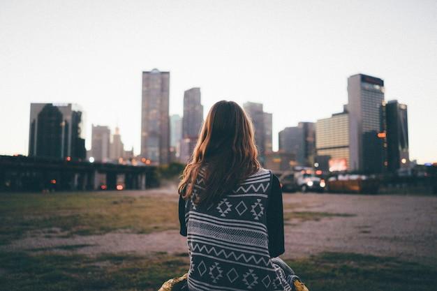 Una ragazza del viaggiatore sta guardando l'orizzonte della città e il tramonto