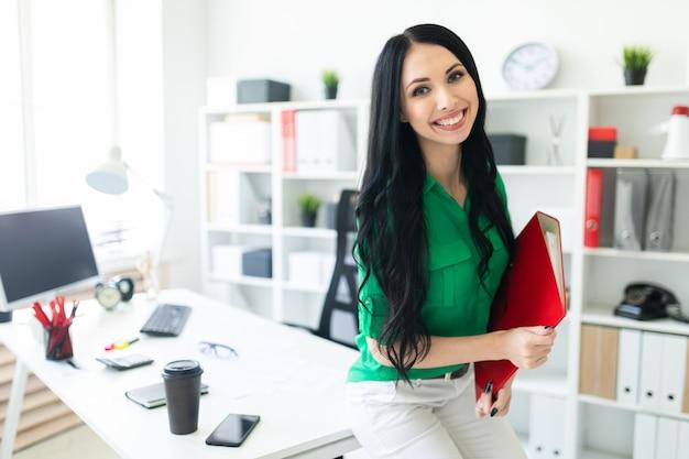 Una ragazza dell'ufficio si sedette sul tavolo e teneva in mano una cartella con i documenti