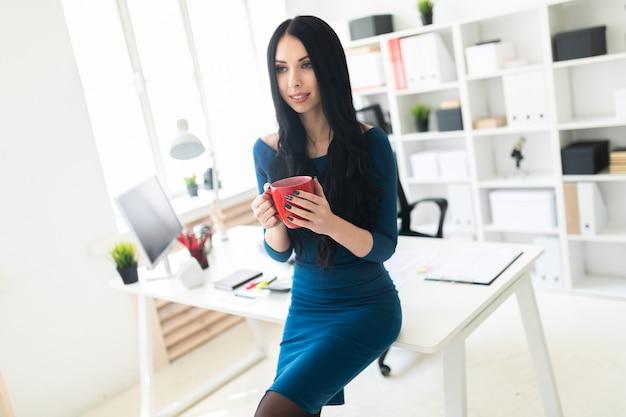 Una ragazza dell'ufficio si sedette sul tavolo e teneva in mano una tazza rossa.