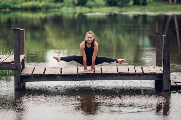 Una ragazza di 13 anni che pratica ginnastica su un ponte del fiume in natura.
