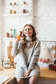 Una ragazza di aspetto europeo è seduta in cucina, getta o tiene in mano agrumi, mandarino, divertimento e divertimento, casa e cucina