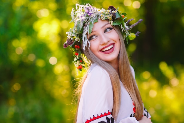 Una ragazza di aspetto slavo con una ghirlanda di fiori selvatici a metà estate.