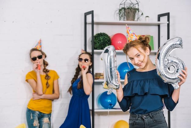 Una ragazza di compleanno che mostra il numero 16 palloncini d'argento della stagnola con i suoi due amici che soffiano il ventilatore di partito
