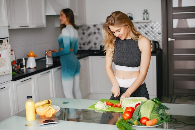 Una ragazza di due sport in una cucina con le verdure