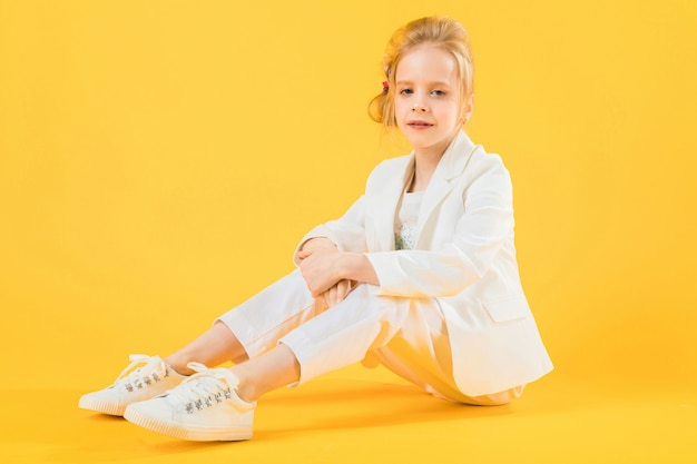 Una ragazza di moda in abiti bianchi siede allungando le gambe in avanti.