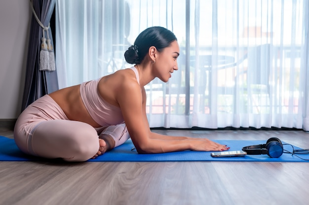 Una ragazza di razza mista sta allungando, seduta nella posizione del loto e allungando in avanti