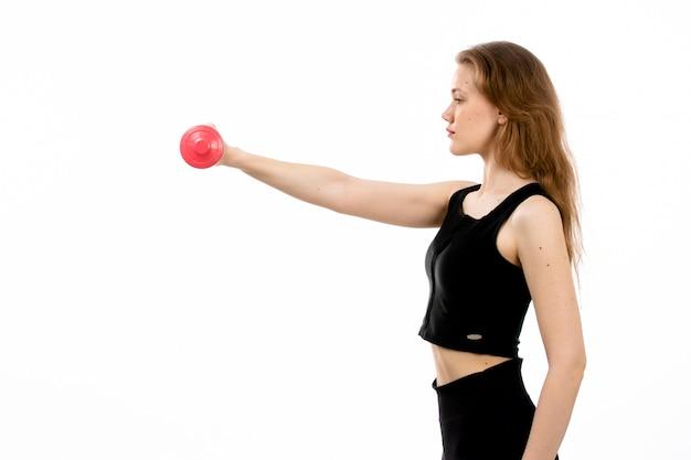 Una ragazza di vista frontale in camicia nera e pantaloni neri che fanno sport con le teste di legno rosse sul bianco