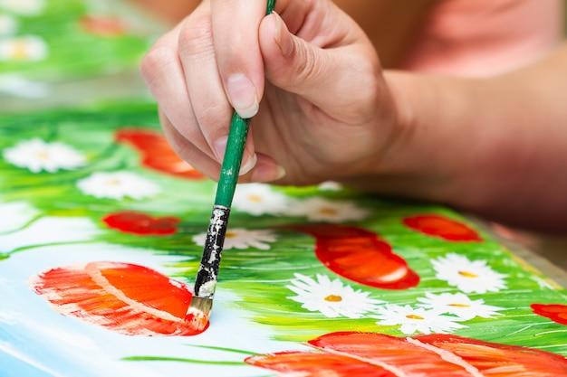 Una ragazza dipinge un'immagine di guazzo. una ragazza che disegna papaveri e camomille. la mano e il pennello