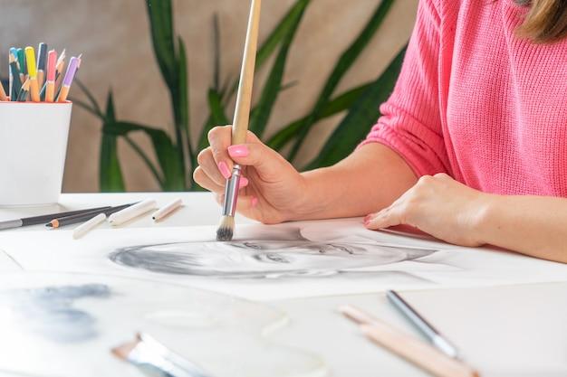 Una ragazza dipinge un ritratto di un uomo in pennello nero nello studio di casa.