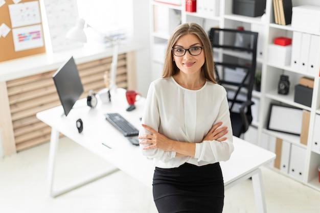 Una ragazza è in piedi appoggiata su un tavolo in ufficio.