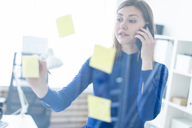Una ragazza è in piedi in un ufficio vicino a una lavagna trasparente con adesivi, parla al telefono e tiene in mano una matita.