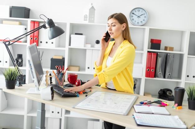 Una ragazza è in piedi vicino a un tavolo, parla al telefono e lavora con un computer. davanti alla ragazza sul tavolo c'è una lavagna magnetica