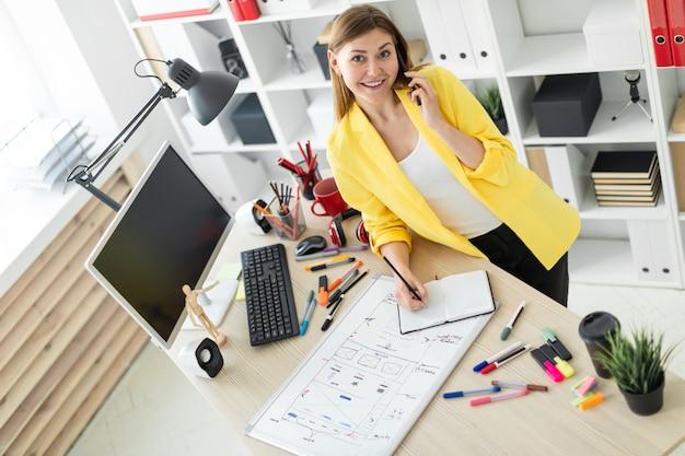 Una ragazza è in piedi vicino a un tavolo, parla al telefono, tiene in mano una matita