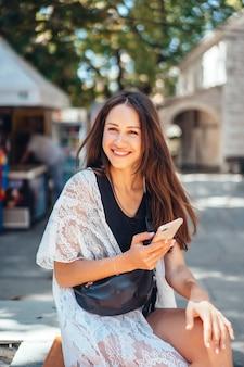 Una ragazza è in possesso di un telefono e in posa sulla fotocamera. la rete. messaggio.