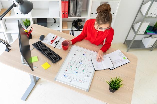 Una ragazza è seduta a un tavolo in ufficio, con in mano una tazza rossa e guardando il blocco note. una lavagna magnetica si trova davanti alla ragazza.