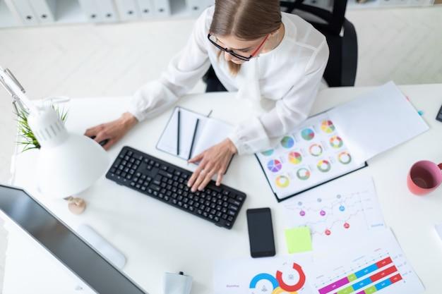 Una ragazza è seduta a un tavolo in ufficio, con una matita in mano e digitando sulla tastiera.