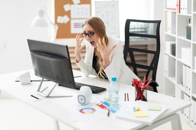 Una ragazza è seduta a un tavolo in ufficio, guarda il monitor e piega le dita.