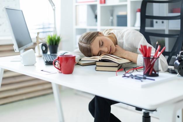 Una ragazza è seduta a un tavolo in ufficio. la ragazza mise la testa sul libro aperto.