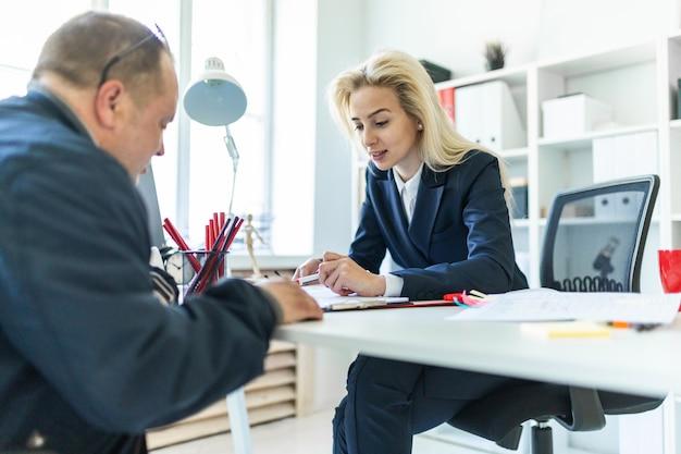 Una ragazza è seduta a un tavolo in ufficio. una ragazza mostra un marcatore in un documento a un uomo.