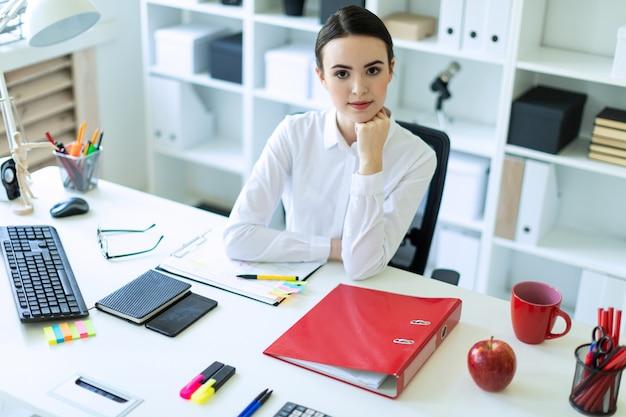 Una ragazza è seduta alla scrivania del computer in ufficio.