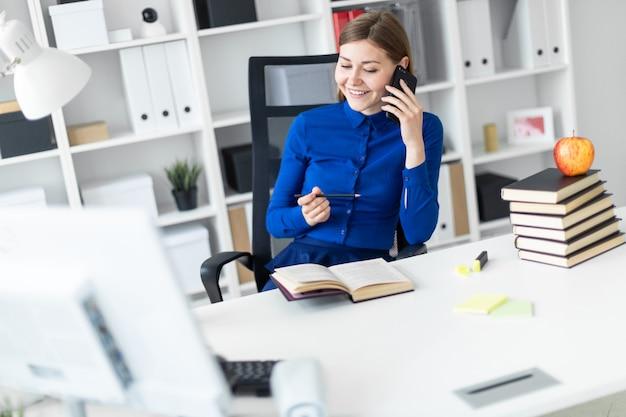 Una ragazza è seduta alla scrivania di un computer, con una matita in mano e parla al telefono.