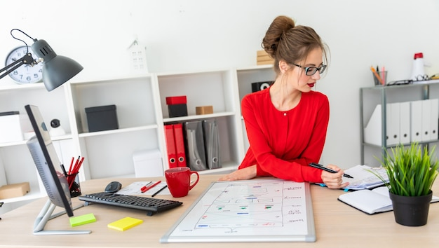 Una ragazza è seduta alla scrivania in ufficio, con in mano un pennarello nero e lavora con un blocco note. una lavagna magnetica si trova davanti alla ragazza.