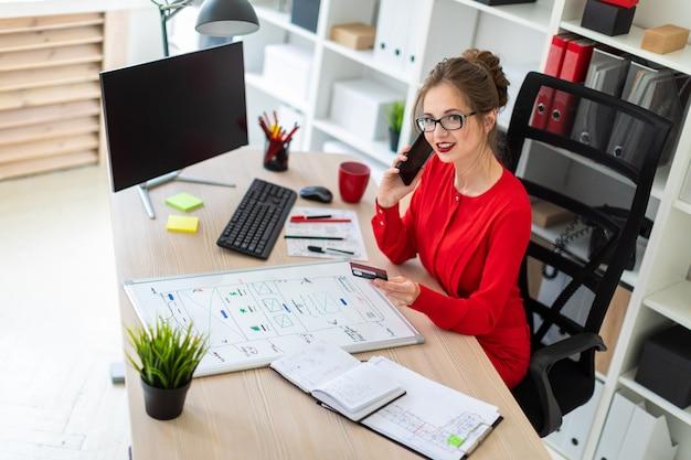 Una ragazza è seduta alla scrivania in ufficio, con in mano una carta di credito e un telefono.
