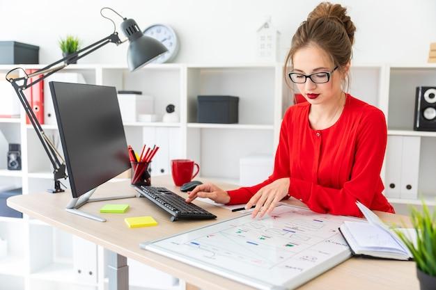 Una ragazza è seduta alla scrivania in ufficio e sta digitando sulla tastiera.