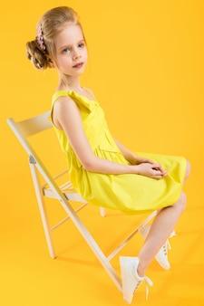 Una ragazza è seduta su una sedia bianca su un muro giallo.