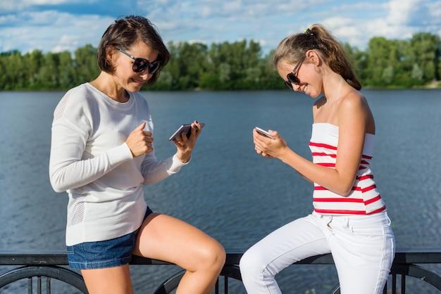 Una ragazza e una madre adolescenti usano i telefoni